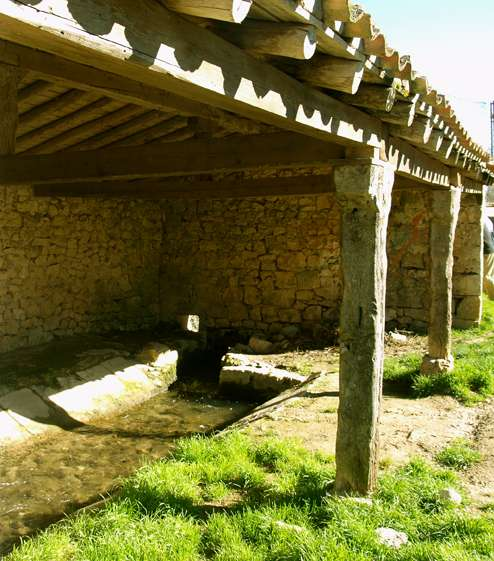 Lavadero en piedra, con cubierta de madera.